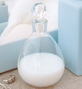 szklany pojemnik na mydło stoi obok błekitnej świecy